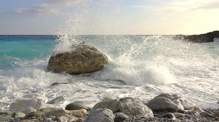 Coastal boulder in the water. Tidal wave breaks into many splashes. Slow motion
