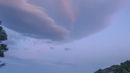 Summer evening on a small rocky beach. Multicolor clouds. Time lapse