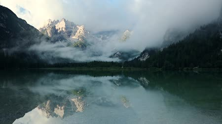 Austria. Summer Alps. Dark mountain lake and fog over sunny peaks. Fast motion