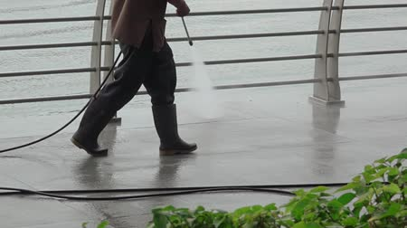 Singapore. Quay Marina Bay. Overcast weather. Worker washes the Embankment. Feet in rubber boots close-up. Slow motion Стоковые видеозаписи