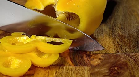 pimentas : Wooden cutting board. A knife cuts a bell pepper. Close up. Slow motion
