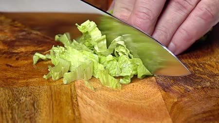 Wooden cutting board. Knife in male hands cuts a bunch of salad. Close up. Slow motion