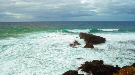 ocean wave break at the rocky shoreline slow motion. Indian Ocean waves break against the rocks of the Gris Gris Beach. Mauritius. 影像素材