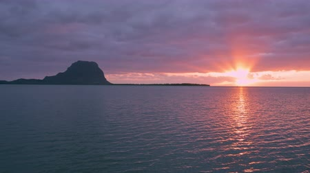 Paradise rocky tropical island at sunset time. Ocean waves and Le Morne Brabant  at sunset time. Mauritius. 影像素材