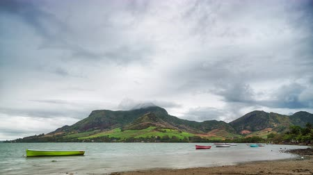 Stormy clouds over volcanic tropical island timelapse. Monsoon from the Indian ocean breaks over the rolling hills descend to the shore, Mauritius.