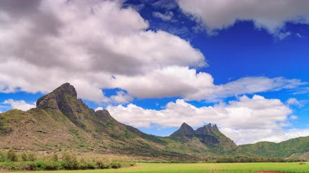 Clouds over paradise rocky tropical island timelapse. Volcanic peaks and the green field island landscape, Mauritius. 影像素材