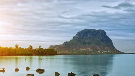 Paradise rocky tropical island at sunset time lapse. Clouds over the Le Morne Brabant at sunset time. Mauritius.