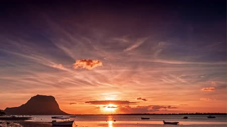 Paradise rocky tropical island at sunset time lapse. Boats on the beach and Le Morne Brabant at sunset time. Mauritius.