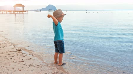 Cute boy throwing pebbles into the sea slow motion. Little boy plays on the beach, Le Morne Brabant Mauritius