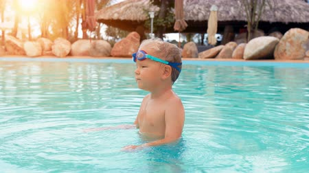 boy with goggles playing in swimming pool in tropical resort slow motion 影像素材
