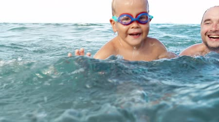 boy and father swim in the sea slow motion. small boy in swimming goggles and his father having fun in the sea 影像素材