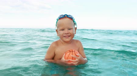 happy boy plays with ball in the sea slow motion. boy in swimming goggles having fun in the sea 影像素材