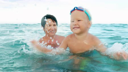 happy boy makes splash in the sea slow motion. boy in swimming goggles and his mother having fun in the sea