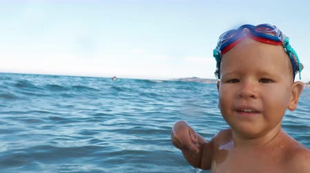 happy boy smiling, looking at camera making splash in sea slow motion. boy in swimming goggles having fun in the sea 影像素材
