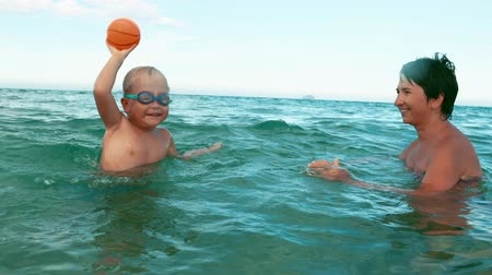 boy and mother plays with ball in the sea slow motion. boy in swimming goggles and his mother having fun in the sea