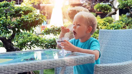 Boy eating ice cream. Happy boy eating ice cream at outdoor cafe on a bright sunny day slow motion 影像素材