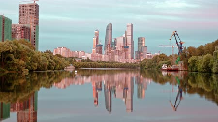 Hyperlapse view on the Moscow City from the boat. Moscow International Business Centre and its reflection in the river at sunset time. Crane unload sand from barge on foreground. 影像素材