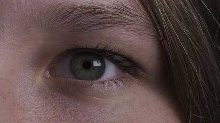 закрывать : closeup dark footage of open and blinking green teen girl eye in 180fps slow motion
