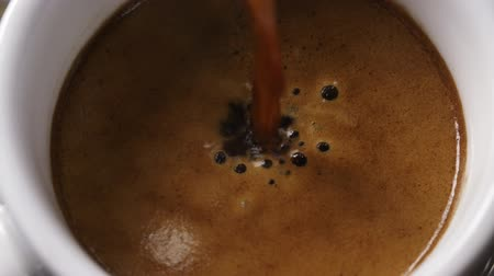 slow motion pouring coffee from espresso machine to cup from above Stock Footage