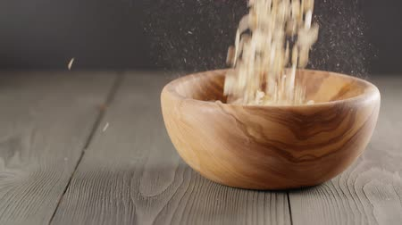 yulaf ezmesi : oat flakes falling into wood olive bowl closeup slow motion footage Stok Video