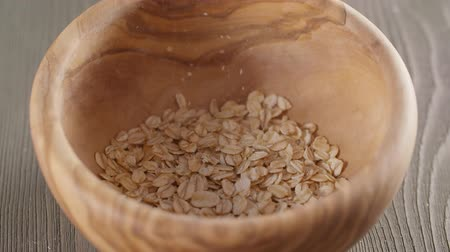 cereais : oat flakes falling into wood olive bowl closeup slow motion footage Vídeos