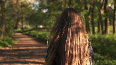 walk behind : teen girl walking in park in sunset from behind shot with stabilizer