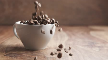 coffe : roasted coffee beans falling in slow motion into cappuccino cup and poured out on table, 180fps Stock Footage