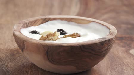 wallnut : nuts and fruits mix falling into yougurt cream in bowl on table in slow motion Stock Footage