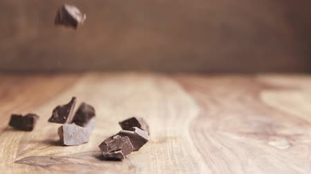 кусок : chocolate chunks falling on wooden table in slow motion