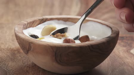 wallnut : eat nuts and fruits mix with yogurt cream in bowl on table in slow motion