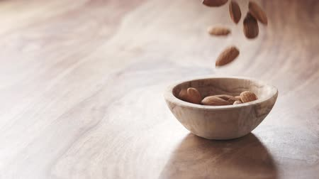 mandula : almonds falling in wood bowl on wooden table in slow motion Stock mozgókép