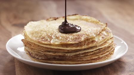 Slow motion of premium dark chocolate pour on freshly made blinis or crepes, 180fps prores footage Stock mozgókép