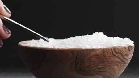 common salt : Slow motion of coarse sea salt crystal falling from spoon to bowl, 180fps
