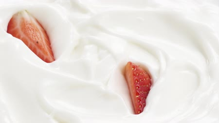 йогурт : Slow motion of sliced strawberry falling into yogurt, 180fps footage