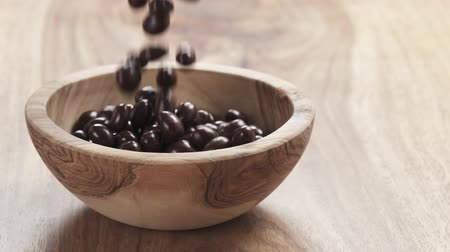 dragee : Slow motion of pine nuts covered with chocolate fall in wood bowl on wooden table, 180fps  footage