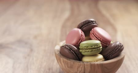 macarons : mixed macarons in wood bowl back slide reveal on table, 4k