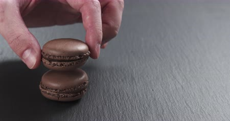 macarons : Slow motion of man hand stacking chocolate macarons on slate board, 4k