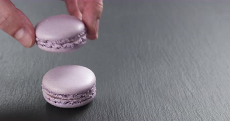 macarons : Slow motion of man hand stacking lavender violet macarons on slate board, 4k