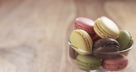 macarons : mixed macarons in glass bowl back slide reveal on table, 4k