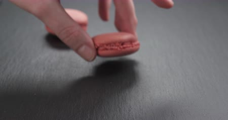 macarons : Slow motion of man hand bring strawberry macarons on slate board, 4k