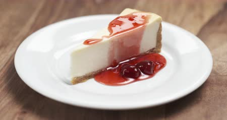 sajttorta : Slow motion of strawberry jam drains over traditional new york cheesecake Stock mozgókép