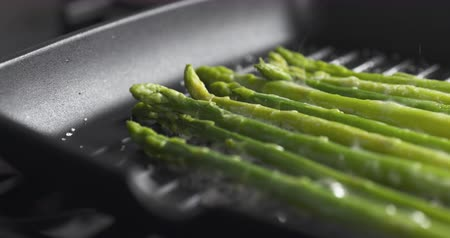 espargos : Slide slow motion shot of cooking frozen green asparagus on grill pan, 4k 60fps footage