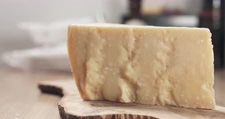 parmigiano : slide piece of hard parmesan cheese on olive board