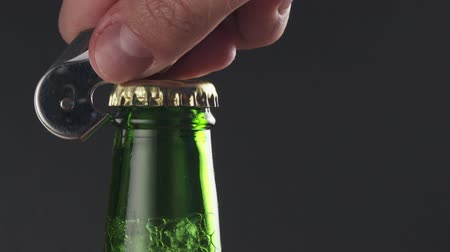 abridor : Slow motion man hand opening green beer bottle