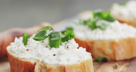 bruschetta : crunchy baguette slices with cream cheese and green onion on olive board