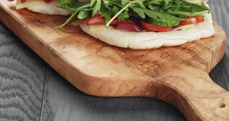 meat pockets : rustic sandwiches with ham arugula and tomatoes in pita bread, on wood table
