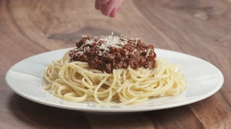 spagetti : Slow motion man hand sprinkle spaghetti bolognese with grated aged parmesan cheese