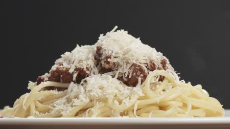 parmigiano : Slow motion salami sausage slices falling on spaghetti bolognese sauce Stock Footage