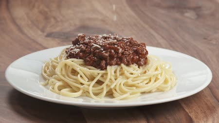 spagetti : Slow motion sprinkle spaghetti bolognese with grated aged parmesan cheese Wideo