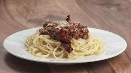 spagetti : Slow motion sundried tomatoes fall on spaghetti bolognese with grated aged parmesan cheese Wideo